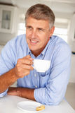 Mid age man with coffee. At home smiling off camera Royalty Free Stock Photo
