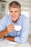 Mid age man with coffee at home. Smiling at camera Stock Photos