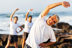 Mid age man exercising. Happy mid age men exercising at the beach with his family Royalty Free Stock Photos
