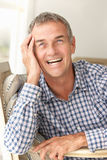 Mid age man head on hand. Smiling Royalty Free Stock Image