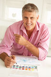 Mid age man painting. Portrait of happy mid age man painting with watercolors smiling at camera Stock Images