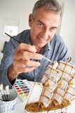 Mid age man painting a model ship at home Stock Photography