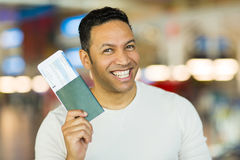Mid age man passport. Cheerful mid age man holding passport and boarding pass at airport Stock Images