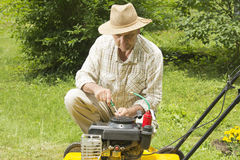 Mid age man repairing lawn mower Stock Photography