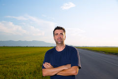 Mid age man in road at meadows posing crossed arms Royalty Free Stock Photography