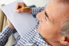 Mid age man sketching. With pencil and note pad Royalty Free Stock Photo