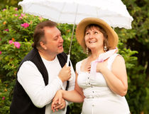 Mid age plus size couple having date in the park. Sunny day Royalty Free Stock Image