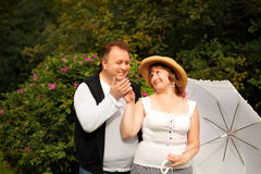 Mid age plus size couple having date in the park. Sunny day Stock Images