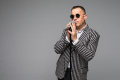 The mid age Showman interviewer with emotions. Young elegant mature man holding microphone against white background. Showman conce. The mid age Showman stock photography