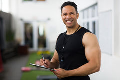 Mid age trainer. Portrait of handsome mid age trainer holding clipboard Stock Images