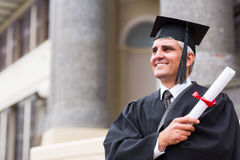 Mid age univeristy graduate. Handsome mid age university graduate standing in front of school building Royalty Free Stock Photo