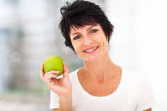Mid age woman apple. Healthy mid age woman holding apple closeup stock photo