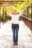 Mid age woman arms outstretched. Happy mid age woman with arms outstretched outdoors royalty free stock photo