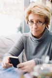 Mid age woman with cell phone sitting cafe Stock Photography