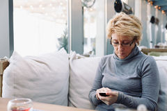 Mid age woman with cell phone sitting cafe Royalty Free Stock Photo