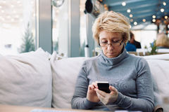 Mid age woman with cell phone sitting cafe Stock Photo