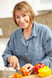 Mid age woman chopping vegetables. Smiling at camera Stock Photo