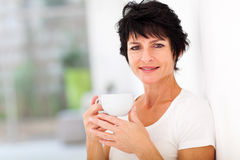 Mid age woman coffee. Attractive mid age woman enjoying coffee at home royalty free stock photo
