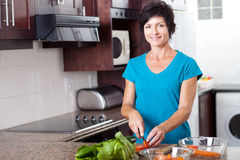 Mid age woman cooking. Attractive mid age woman cooking in kitchen stock photography