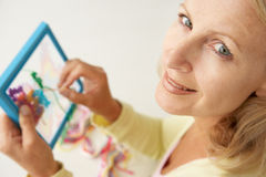 Mid age woman doing cross stitch. Portrait of mid age woman doing cross stitch smiling at camera stock photography