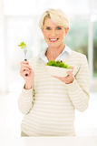 Mid age woman eating salad. Happy mid age woman eating green salad at home Royalty Free Stock Photo