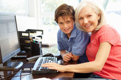 Mid age woman and grandson using computer Stock Image