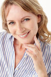 Mid age woman head and shoulders. Smiling at camera royalty free stock images