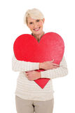Mid age woman hugging heart Stock Image