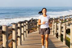 Mid age woman jogging. Fit mid age woman jogging at the beach in the morning royalty free stock photos