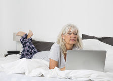 Mid Age woman with a laptop in bed Stock Images