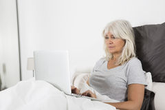 Mid Age woman with a laptop in bed Royalty Free Stock Images