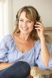 Mid age woman listening to music. Mid age woman wearing headphones listening to music stock photo