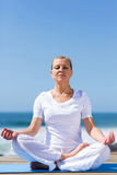 Mid age woman meditating. Peaceful mid age woman meditating by the beach stock image
