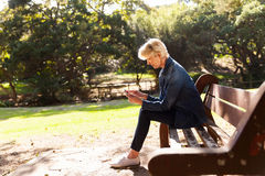 Mid age woman park. Mid age woman using smart phone at the park sitting on a bench stock photography