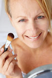 Mid age woman putting on make-up. Smiling at camera royalty free stock images