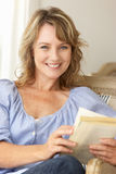 Mid age woman reading a book. Smiling at camera royalty free stock photo