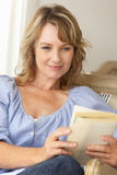 Mid age woman reading book. Portrait of mid age woman reading book stock images