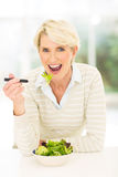 Mid age woman salad. Beautiful mid age woman eating fresh vegetable salad at home Stock Images
