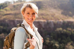 Mid age woman standing. Happy mid age woman with backpack standing on top of the mountain stock images