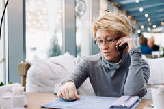 Mid age woman talking on cell phone sitting cafe Royalty Free Stock Images