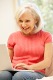 Mid age woman using laptop at home Royalty Free Stock Photos