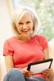 Mid age woman using tablet at home Royalty Free Stock Images