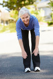 Mid age woman warming up for run Stock Photography