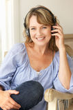 Mid age woman wearing headphones. Smiling royalty free stock photos