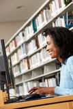 Mid age woman working on computer in library Royalty Free Stock Photography