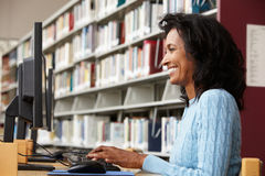 Mid age woman working on computer in library Stock Image