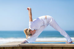 Mid age woman yoga. Flexible mid age woman doing yoga pose on beach royalty free stock photo