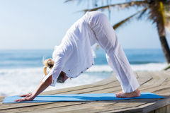 Mid age woman yoga. Healthy mid age woman yoga exercise outdoors on beach royalty free stock photos