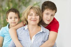 Mid-age woman with two boys indoor stock image