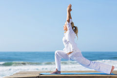 Mid age yoga. Peaceful mid age woman doing yoga exercise on beach Stock Photography